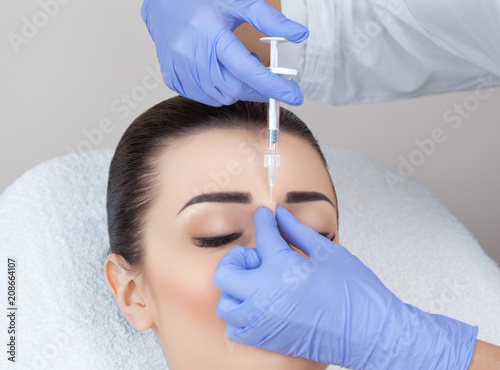 The doctor cosmetologist makes the Rejuvenating facial injections procedure for tightening and smoothing wrinkles on the face skin of a beautiful, young woman in a beauty salon.Cosmetology skin care. © Dimid