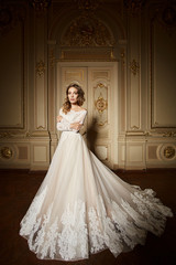 Fashion portrait of beautiful woman in long elegant white dress. Girl with elegant hairstyle. Bridal fashion model in luxury interior in the Baroque style © sarymsakov.com