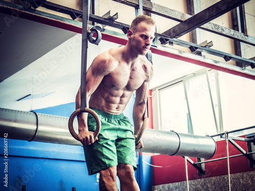 Poster Handsome muscular young man athlete exercising in gym, hanging and pushing up with rings. Tattoo reads: Life is a carnival. And: Noise.
