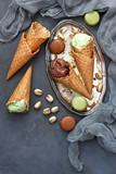 Variety of ice cream  in cones with chocolate and pistachio