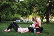 Two young women with phone relaxing in a park