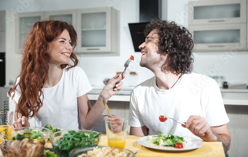 Taste this one. Joyful young woman is feeding her husband by a piece of tomato. She is laughing while sitting at table in cook room  - 208675535