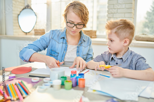 Foto Murales Pretty young tutor in casualwear teaching cute little pupil how to use scissors correctly while making creative present for Fathers Day, interior of modern classroom on background