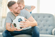 Cheerful family of football lovers enjoying each others company at home while taking break from playing football,  interior of cozy living room on background - 208677178