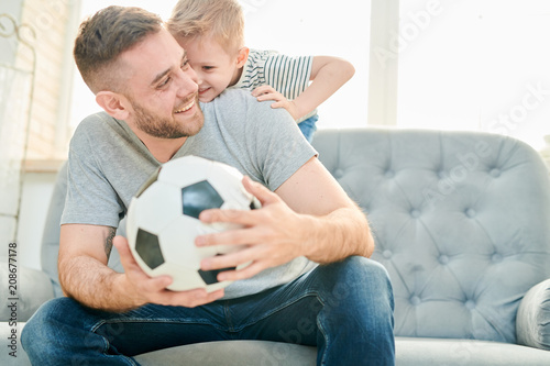 Cheerful family of football lovers enjoying each others company at home while taking break from playing football, interior of cozy living room on background