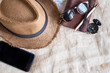 Top view of Summer brown panama straw hat,mobile,sunglasses,notebook map,compass on linen cloth.vacation travel concept.copy space for adding text.
