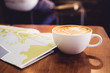 White coffee cup with latte art with travel map on brown wood table,Leisure activity.