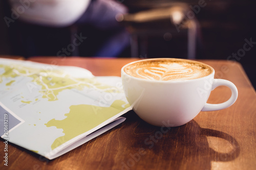 Wall mural White coffee cup with latte art with travel map on brown wood table,Leisure activity.