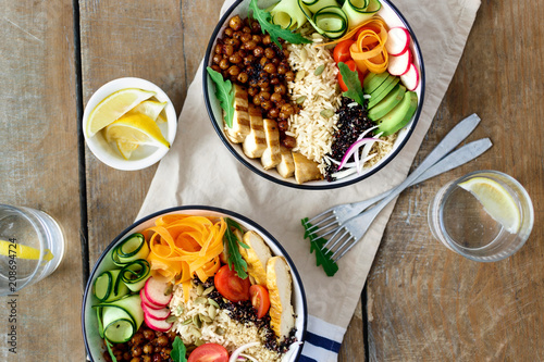 Top view two buddha bowl lemon water Clean balanced healthy food concept Chicken grilled steak rice spicy chickpeas black white quinoa avocado carrot zucchini radish tomatoes wooden table - 208694724