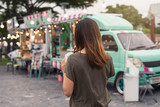 Young asian woman walking in the food truck market - 208697952