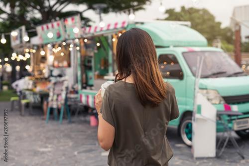 Foto Murales Young asian woman walking in the food truck market
