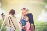 Mother and daughter drawing picture together in the park - 208699192