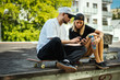 boy and girl on a skateboard are sitting and watching something on the mobile phone on a summer day - 208702999