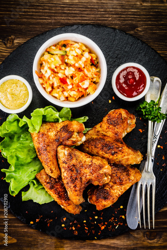 Chicken wings with French fries on wooden background  - 208702910