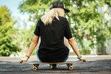 girl in a black T-shirt is sitting with her back on a skateboard and looks around - 208703323