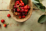 Cherries in a rustic basket and branch