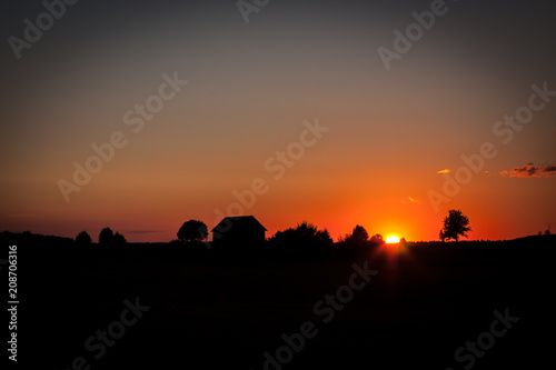 A picturesque sunset with a barn's silhouette