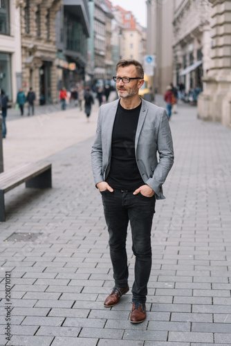 Mature professional man standing in urban scene