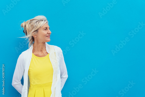 Relaxed confident blond woman against a blue wall © contrastwerkstatt