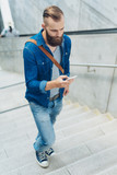 Bearded man walking upstairs using a mobile phone