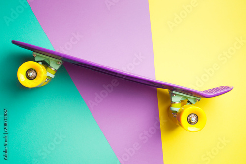 violet skateboard with yellow wheels on turquoise yellow and purple background. plastic mini cruiser board. pastel creative concept. minimalism, flat lay, copy space
