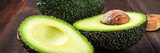 Cut and whole avocado on a wooden board on a brown background. banner