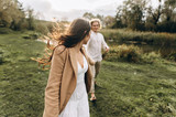 A beautiful couple in free clothes walks in the lawn near the lake on a sunny summer day - 208714526