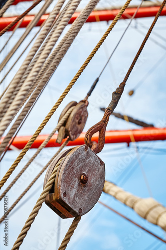Close up picture of old sailing ship wooden pulley, selective focus.