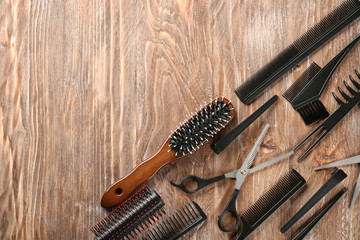 Flat lay composition with set of hairdresser's tools on wooden background