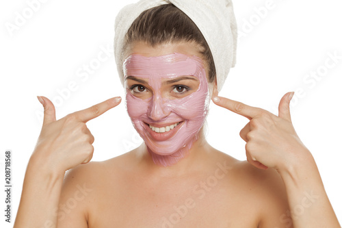 Fotobehang Spa young smiling woman pointing on her facial mask on her face with a towel on her head
