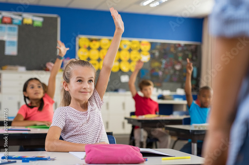 Children raising hands in classroom - 208721776