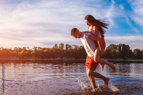 Fototapeta Young man and woman running on summer river bank. Couple having fun at sunset. Guys chilling