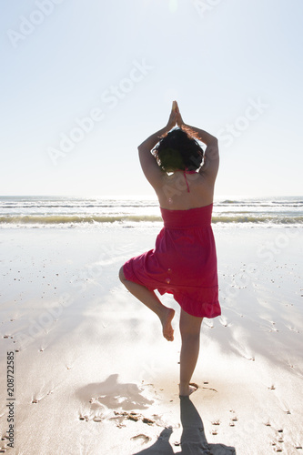 back view of woman make exercises yoga on sunset beach summer