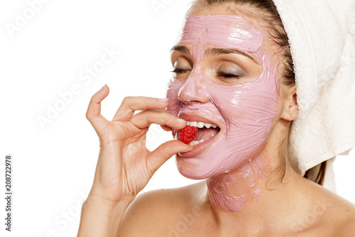 Foto Murales young smiling woman posing with  facial fruit  mask on her face , and with raspberry on her mouth