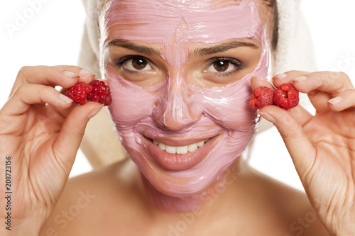 young smiling woman posing with facial fruit mask on her face , and with raspberryes on her hands