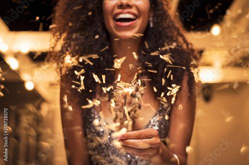 Foto Murales Woman holding fire sparkler