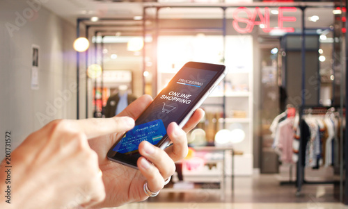 Man using mobile payments online shopping network connection on screen, Mall department store background. All on screen and credit card are designed up.