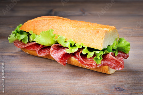 Half baguette sandwich with salami and lettuce