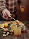 Ginger tea with honey , lemon and mint on old wooden table . - 208736572