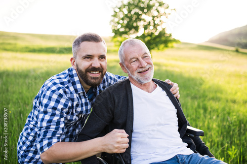 An adult hipster son with senior father in wheelchair on a walk in nature at sunset, laughing. - 208736507