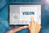 A hand selecting a Vision business concept on a computer tablet screen with a colorful background. - 208739769