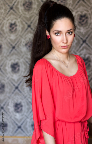 portrait of beautiful girl in  silk orange dress, old  decorated wall background