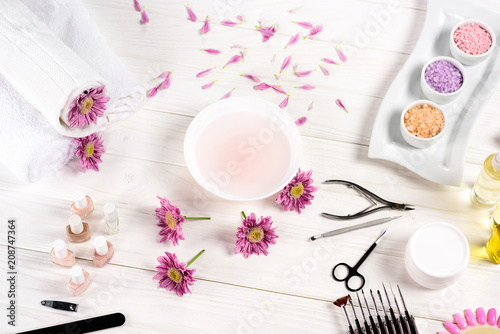 elevated view of bath for nails at table with flowers, petals