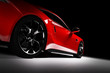 Modern red sports car in a spotlight on a black background. - 208747506