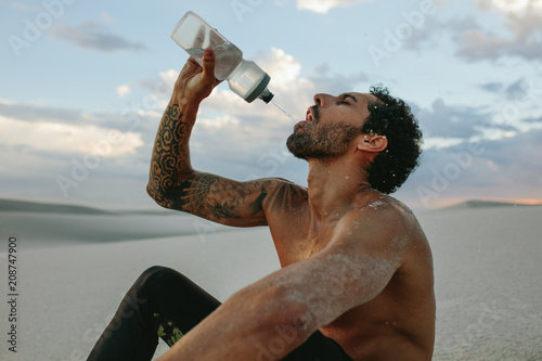Athlete getting hydrated after workout in desert