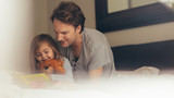 Father and daughter reading a story book - 208748519
