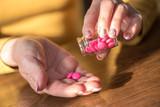 Female hands taking medication, hard light