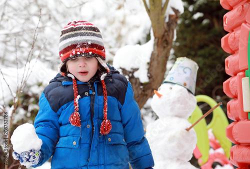 Foto Murales Petit garçon joue dehors avec la neige. Hiver, bonhomme de neige