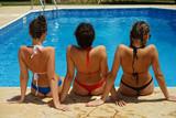three women in bikinis by swimming pool