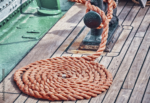 Vintage toned picture of a rope on an old sailing ship wooden deck.